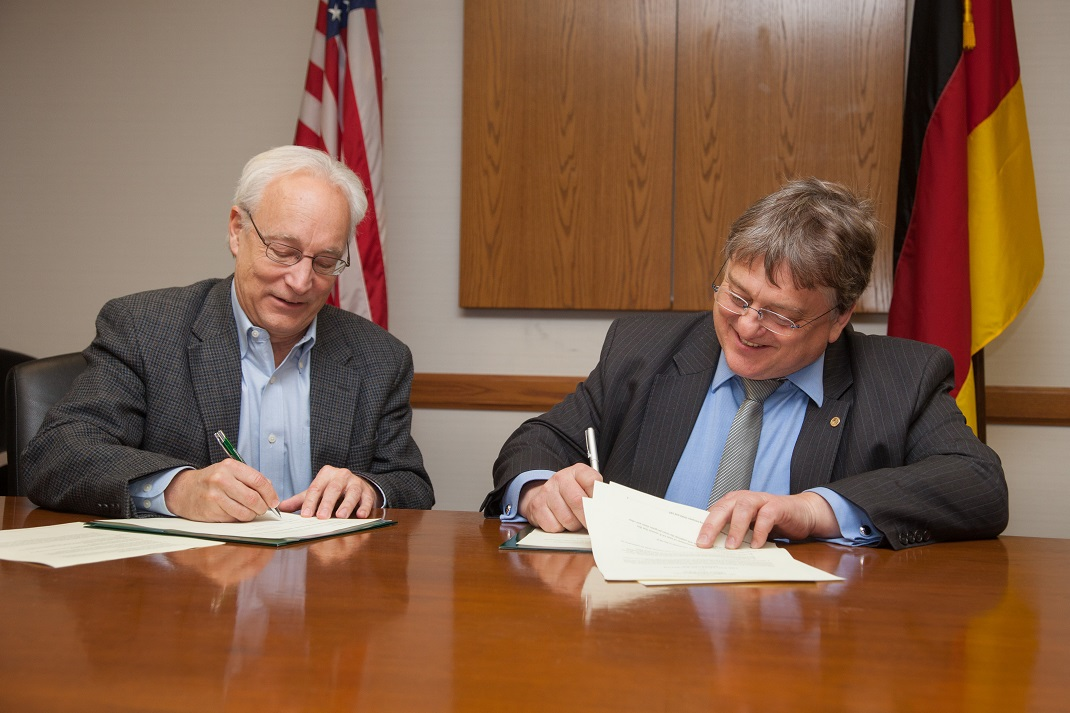 Dean Hugh Sherman and Dean Herbert Woratschek sign the addendum